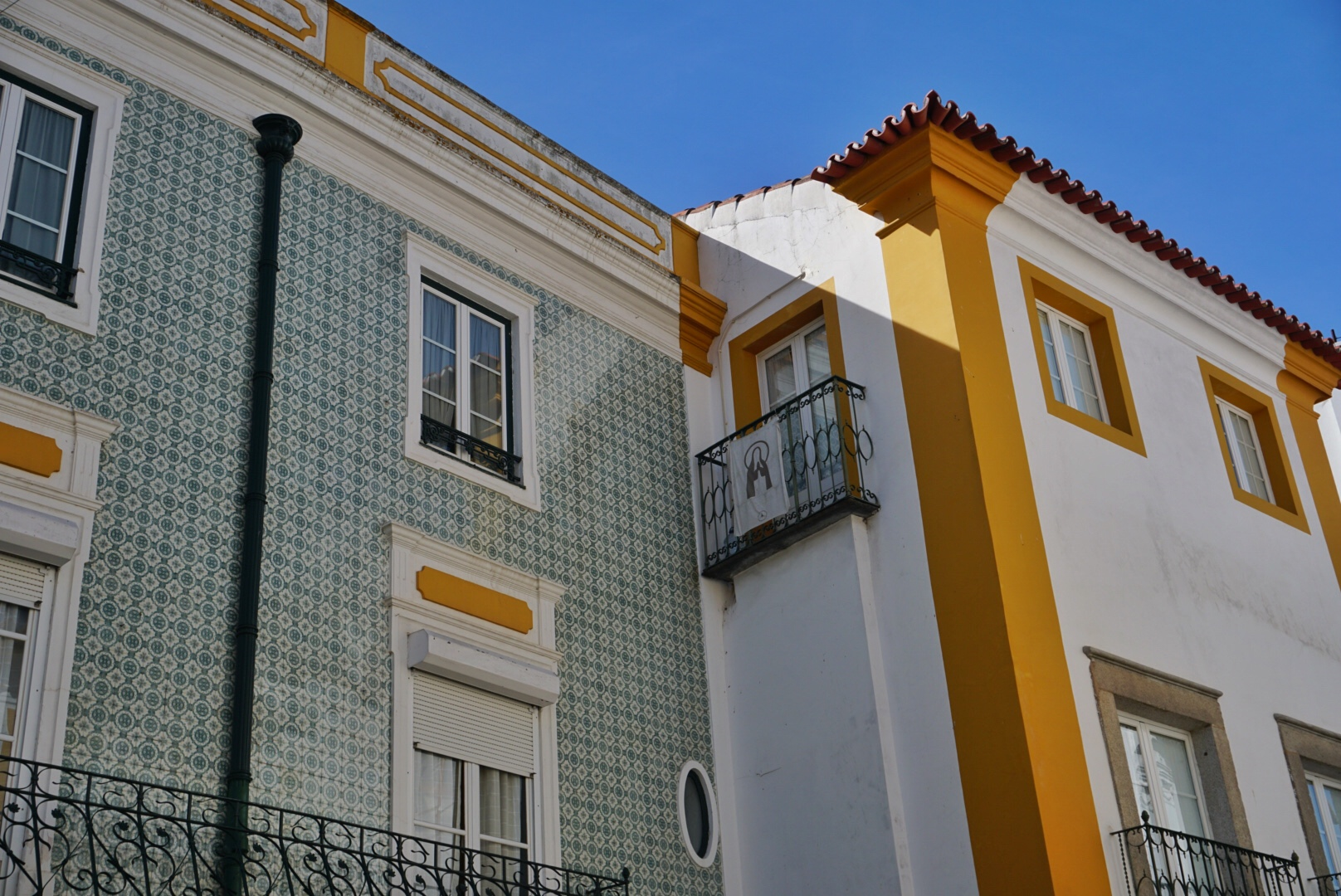 Portugese typische huizen, roadtrip Alentejo Portugal. Blauwe groene tegeltjes, gele accenten